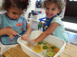 Toddler friends sharing sensory water exploration with lemons, limes and oranges!🍋🍈🍊